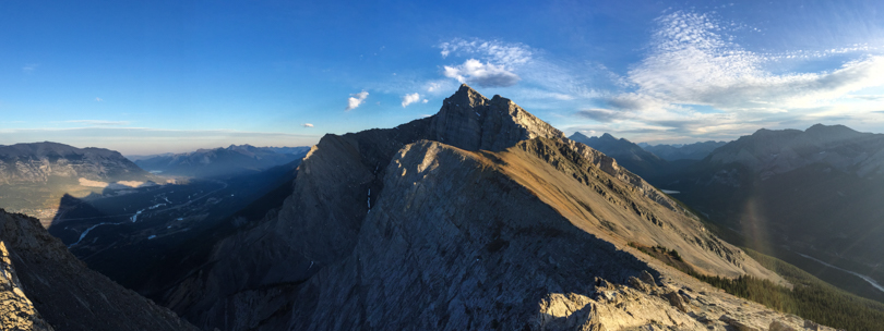From Ha Ling Peak: Mountain peaks all around and Canmore down below